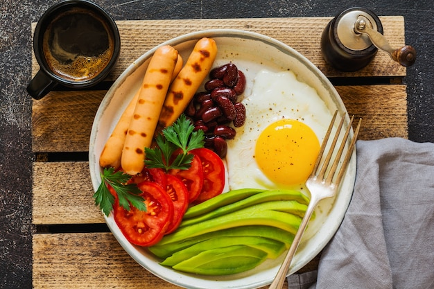 Traditionelles englisches frühstück mit spiegeleiern, avocado, wurstgrill, bohnen und tomaten auf dunkler betonoberfläche
