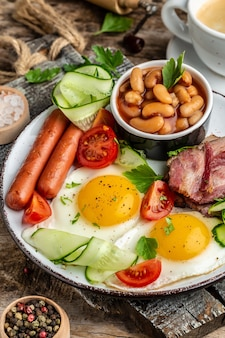 Traditionelles englisches frühstück mit spiegeleiern, speck, bohnen, kaffee und wurst, menü im restaurant, diät, kochbuchrezept. vertikales bild.