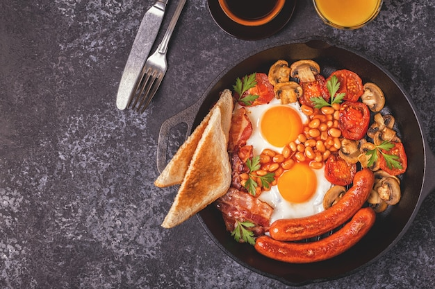 Traditionelles englisches frühstück mit spiegeleiern, würstchen, bohnen, pilzen, gegrillten tomaten und speck. ansicht von oben.