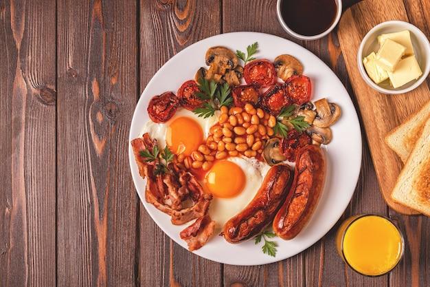 Traditionelles englisches frühstück mit spiegeleiern, würstchen, bohnen, pilzen, gegrillten tomaten und speck auf holzhintergrund. ansicht von oben