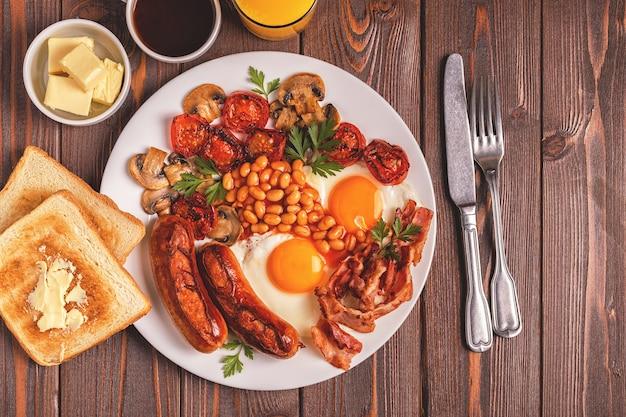 Traditionelles englisches frühstück mit spiegeleiern, würstchen, bohnen, pilzen, gegrillten tomaten und speck auf holzhintergrund