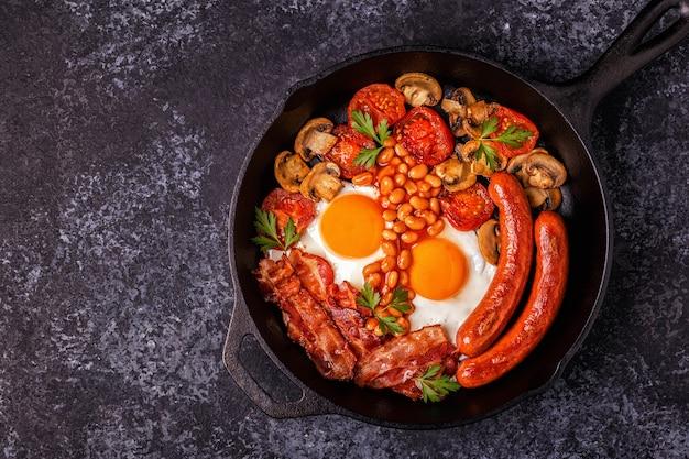 Traditionelles englisches frühstück mit spiegeleiern, würstchen, bohnen, pilzen, gegrillten tomaten und speck.