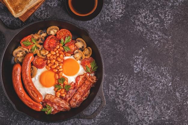 Traditionelles englisches frühstück mit spiegeleiern, würstchen, bohnen, pilzen, gegrillten tomaten und speck
