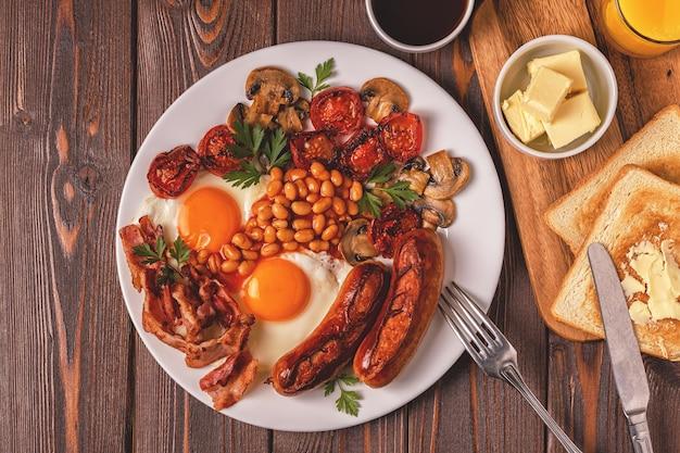 Traditionelles englisches frühstück mit spiegeleiern, würstchen, bohnen, pilzen
