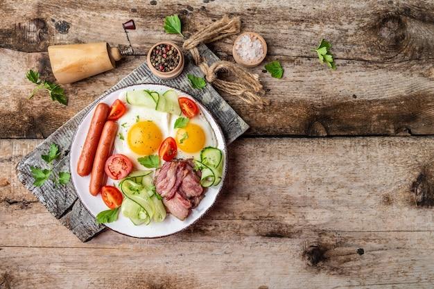 Traditionelles englisches frühstück mit spiegeleiern, würstchen, bohnen, tomaten und speck auf holztisch.