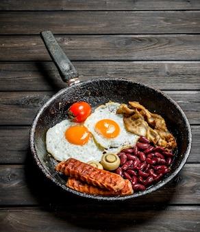 Traditionelles englisches frühstück mit spiegeleiern, würstchen und bohnen. auf einer holzoberfläche.