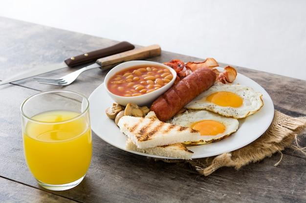 Traditionelles englisches frühstück mit spiegeleiern, würsten, bohnen, pilzen, gegrillten tomaten und speck auf holzoberfläche