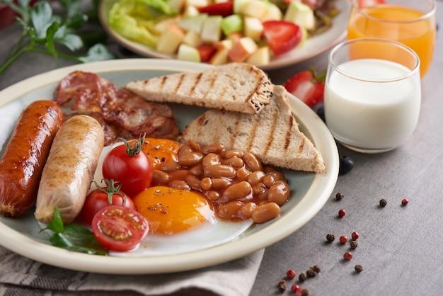Traditionelles englisches frühstück mit spiegeleiern, wurst, tomaten, bohnen, toast und speck auf einem teller