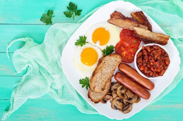 Traditionelles englisches frühstück: speck, pilze, eier, tomaten, würstchen, bohnen, toast auf einem weißen teller auf einem hellen holztisch. draufsicht. england klassische küche.