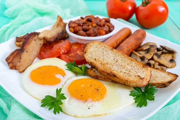 Traditionelles englisches frühstück: speck, pilze, eier, tomaten, würstchen, bohnen, toast auf einem weißen teller auf einem hellen holztisch. england klassische küche.