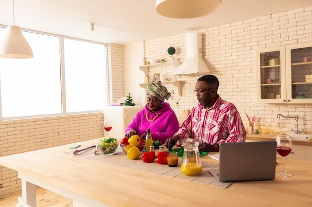 Traditionelles essen. angenehmes afrikanisches paar, das gemüse schneidet, während das mittagessen zusammen kocht
