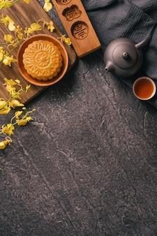Traditionelles essenskonzept des mid-autumn festivals - schöner mondkuchen auf schwarzem schiefertisch mit tee, gebäckform, blume, draufsicht, flacher lage, kopierraum