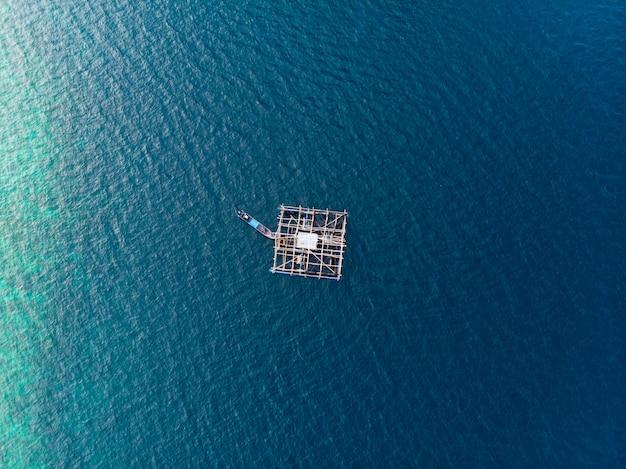 Traditionelles fischerboot der luftspitzen-ansicht unten, das auf tropisches karibisches meer des türkiskorallenriffs schwimmt. indonesien molukken-archipel