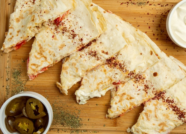 Traditionelles fleischgemüse gutab, qutab, gozleme auf hölzernem brett mit sumakh, turshu und joghurt.