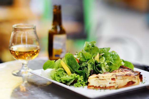 Traditionelles französisches lebensmittel: quiche lorraine und frischer salat verlässt mit glas bier auf hintergrund