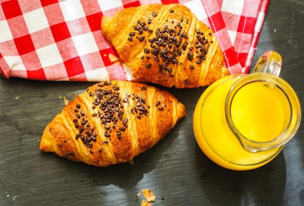 Traditionelles frühstück mit hörnchen und orangensaft