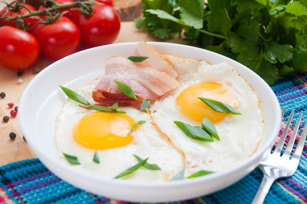 Traditionelles frühstück mit spiegeleiern und speck