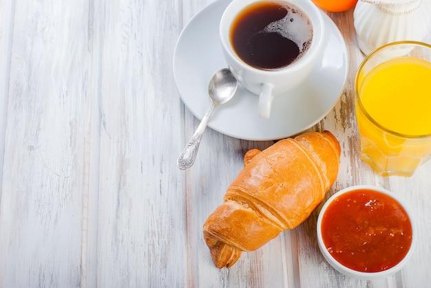 Traditionelles frühstückshörnchen und kaffee, marmelade, orangensaft