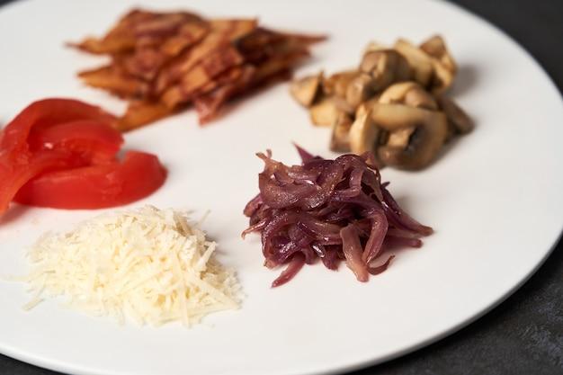 Traditionelles frühstücksomelett mit speck, tomaten, pilzen, zwiebeln