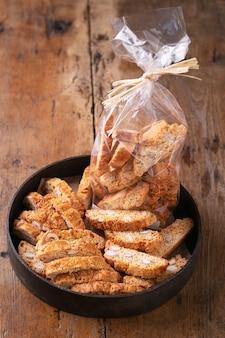 Traditionelles gebäck, italienische selbst gemachte biscottiplätzchen oder cantuccini, mit mandelnüssen auf einem rustikalen