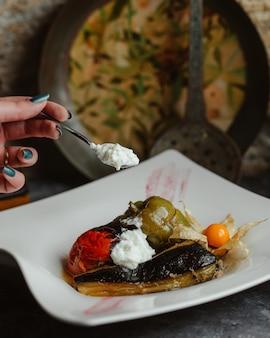 Traditionelles gemüseolma in einer weißen platte mit joghurt