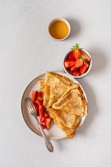Traditionelles gericht für den urlaub maslenitsa. dünne crepes pfannkuchen mit honig, frischen erdbeeren und zutaten für das frühstück. draufsicht.