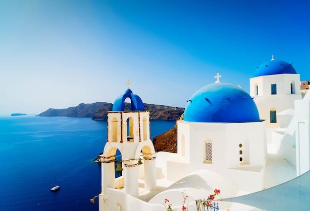 Traditionelles griechisches dorf oia von santorini, mit blauen kuppeln gegen meer und caldera, griechenland, getönt