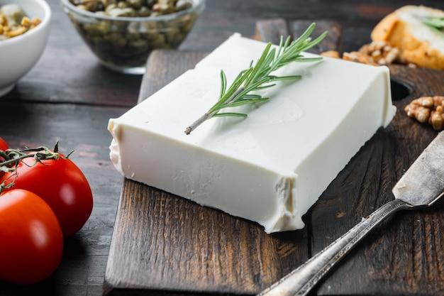 Traditionelles griechisches feta-käse-set auf dunklem holztisch
