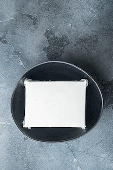 Traditionelles griechisches feta-käse-set, auf grauem tisch, flach gelegt
