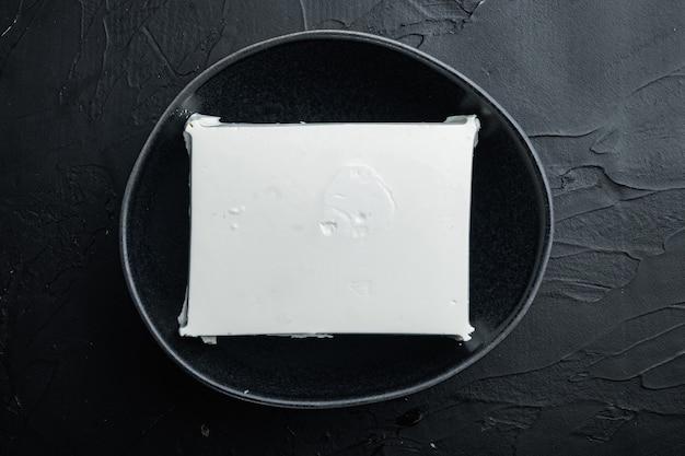 Traditionelles griechisches feta-käse-set, auf schwarzem tisch, draufsicht