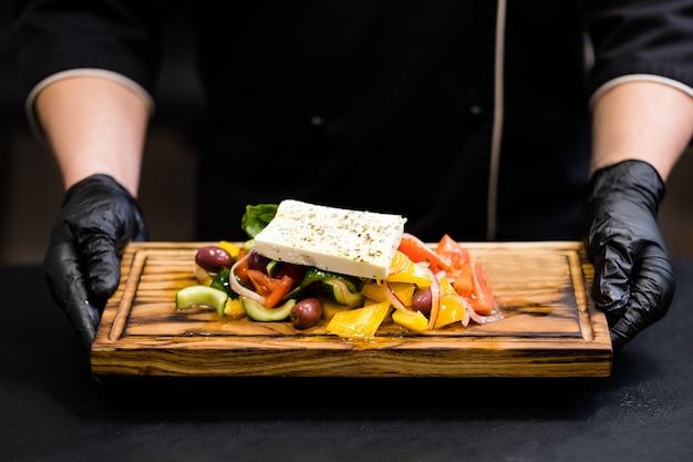 Traditionelles griechisches salatrezept. abgeschnittene aufnahme eines kochs, der ein holzbrett mit frischem gemüse, kalamata-oliven und feta-käse hält.
