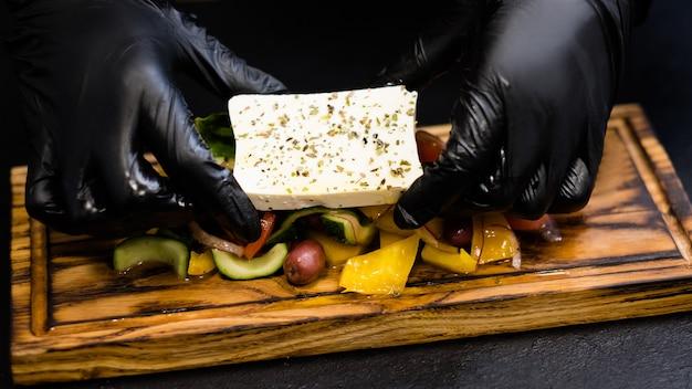 Traditionelles griechisches salatrezept. chef-hände servieren feta-käse gewürzt mit oregano über gemüse auf holzbrett.