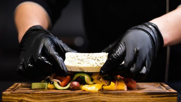 Traditionelles griechisches salatrezept. chefkoch serviert feta-käse mit frischem gemüse auf rustikalem holzbrett.