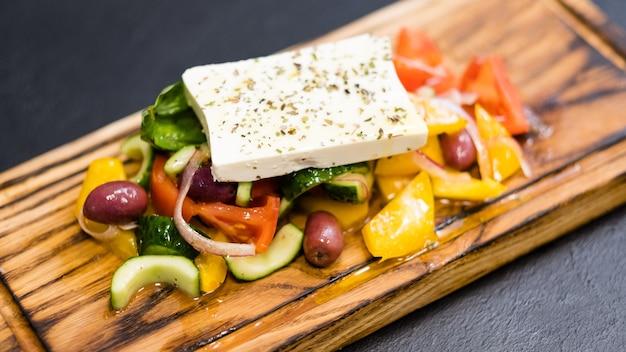 Traditionelles griechisches salatrezept. nahaufnahme von frischem gemüse, kalamata-oliven und feta-käse, gewürzt mit extra nativem öl.