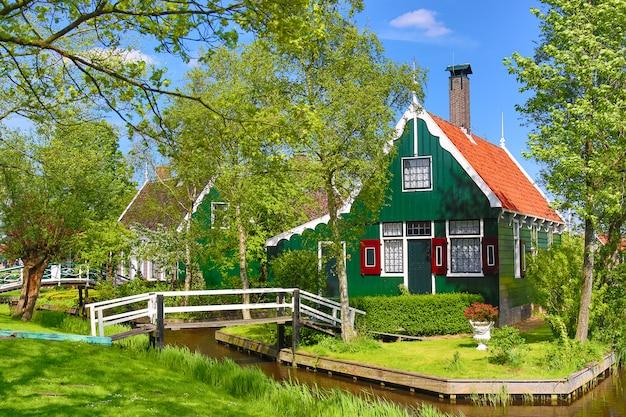 Traditionelles grünes niederländisches haus mit weniger holzbrücke gegen blauen himmel im dorf zaanse schans, die niederlande