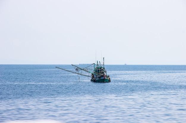 Traditionelles grünes thailändisches fischerboot, das in der bucht von thailand nahe koh chang am tag den hellen himmel schwimmt.