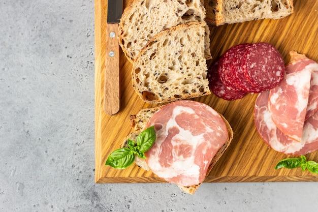 Traditionelles handwerkerbrot mit samen und schweinswurst und salami diente auf einem hölzernen schneidebrett. offenes sandwich mit schweinefleischwurst.