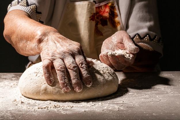 Traditionelles hausgemachtes brot zubereiten. nahaufnahme der alten frau, großmutter, die teig knetet. selbstgemachtes brot. hände, die brotteig auf holztisch vorbereiten