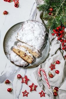 Traditionelles hausgemachtes deutsches weihnachtsbacken-stollen-kuchenbrot auf teller mit weihnachtsdekorationen und tannenzweigen über weißer marmoroberfläche. flach liegen