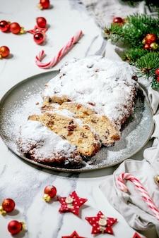 Traditionelles hausgemachtes deutsches weihnachtsbacken-stollen-kuchenbrot auf teller mit weihnachtsdekorationen und tannenzweigen über weißer marmoroberfläche.