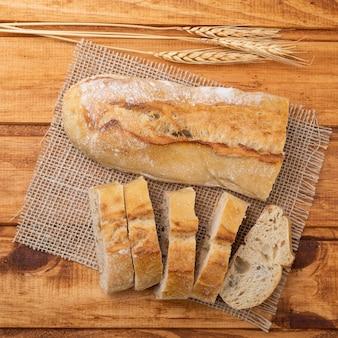 Traditionelles hausgemachtes französisches baguettebrot mit scheiben über holztisch.