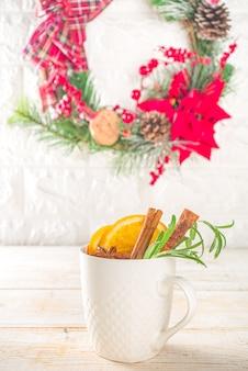 Traditionelles heißes alkoholgetränk im winter. glühwein in einer weißen tasse auf dem hintergrund des küchentisches mit weihnachtsschmuck.