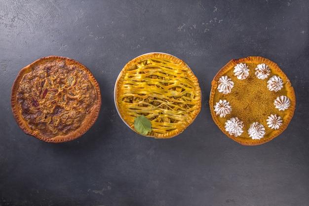 Traditionelles herbstbacken. amerikanische und europäische traditionelle herbst-winter-kuchen - mit kürbis, pekannuss und apfel