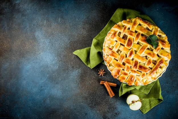 Traditionelles herbstbacken, hausgemachter apfelkuchen mit zimt, dunkelblauer hintergrund mit brötchen, zuckerpulver, frische äpfel, gewürze,