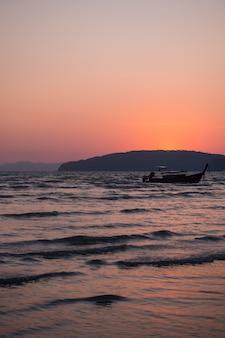 Traditionelles hölzernes thailändisches passagierboot des langen schwanzes auf meer am abend