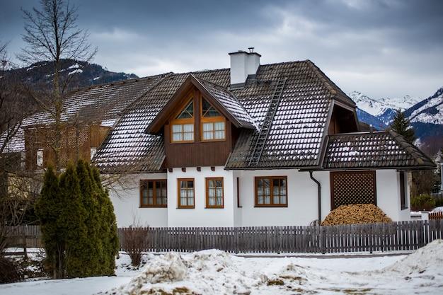 Traditionelles holzhaus in den österreichischen alpen am verschneiten tag