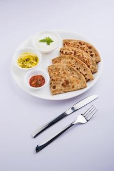 Traditionelles indisches essen aloo paratha oder kartoffel gefülltes fladenbrot. serviert mit tomatenketchup und quark auf buntem oder hölzernem hintergrund. selektiver fokus