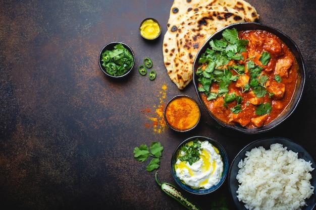 Traditionelles indisches gericht chicken tikka masala mit platz für text. würziges curryfleisch in schüssel, basmatireis, brot naan, joghurt-raita-sauce auf rustikalem dunklem hintergrund, draufsicht, nahaufnahme, kopierraum