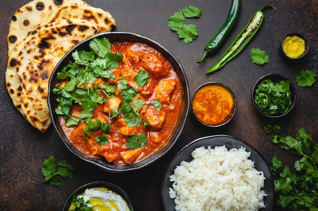 Traditionelles indisches gericht chicken tikka masala mit würzigem curryfleisch in schüssel, basmatireis, brot naan, joghurt-raita-sauce auf rustikalem dunklem hintergrund, draufsicht, nahaufnahme. abendessen nach indischer art von oben