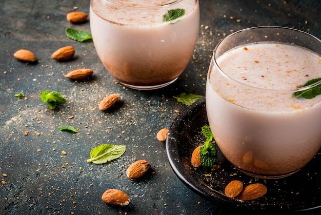 Traditionelles indisches getränk, holi-festivallebensmittel, milchgetränk thandai sardai mit nüssen, gewürze, minze. dunkelblaue oberfläche, kopienraum